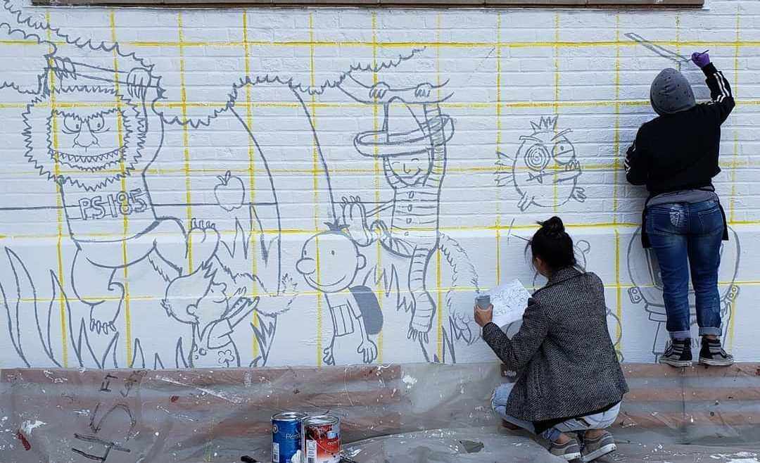 artists painting children's characters on wall