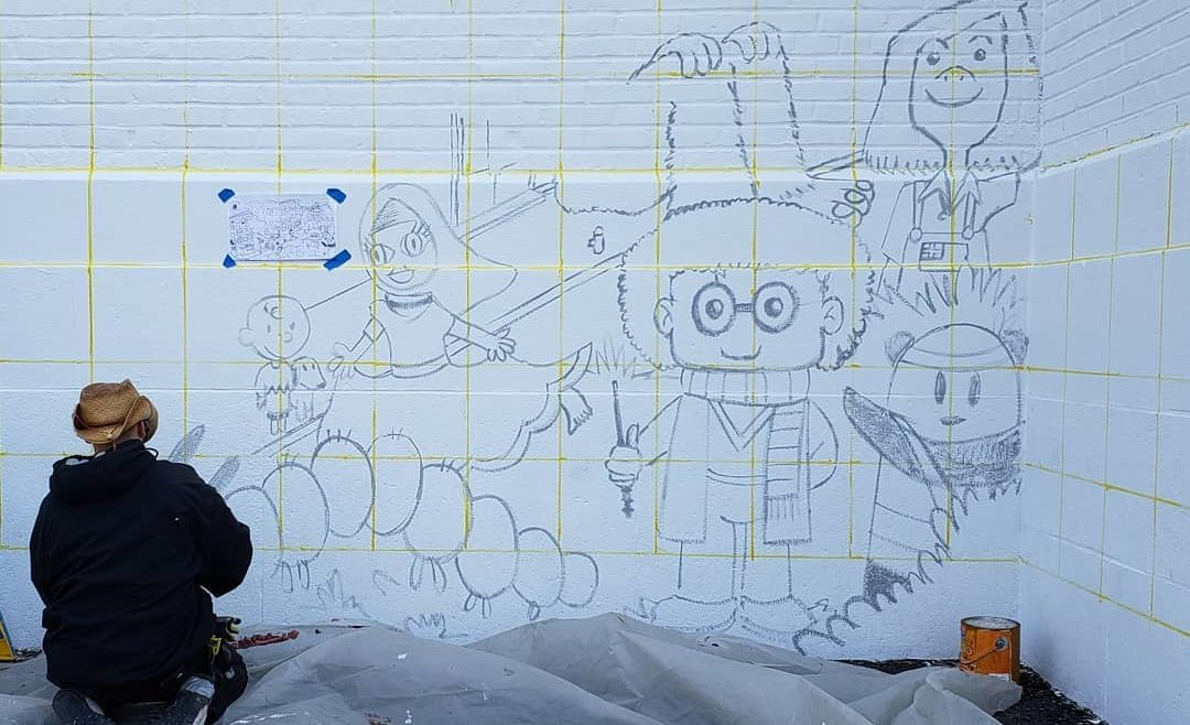 artist painting children's drawings on wall