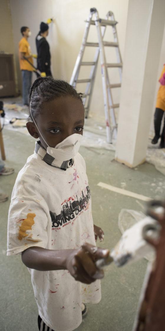 kid volunteering to paint wall