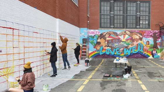 artists painting mural on wall