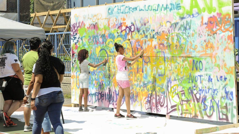 kids spray painting wall