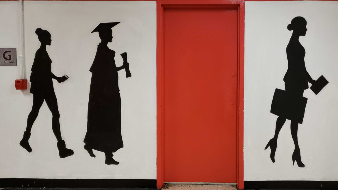 graduate silhouettes painted on school wall